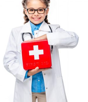 smiling schoolchild in costume of doctor holding first aid kit isolated on white